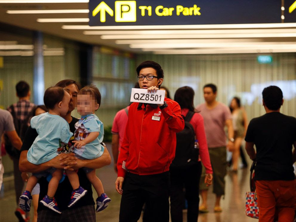 PHOTO: A Changi Airport staff member holds up a sign to direct possible next-of-kins of passengers of AirAsia flight QZ 8501 from the Indonesian city of Surabaya to Singapore, at Changi Airport in Singapore, Dec. 28, 2014.