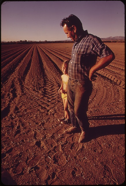 Cotton farmer, John Vanderslice, and his daughter stand on newly planted field, May 1972 by The U.S. National Archives, via Flickr