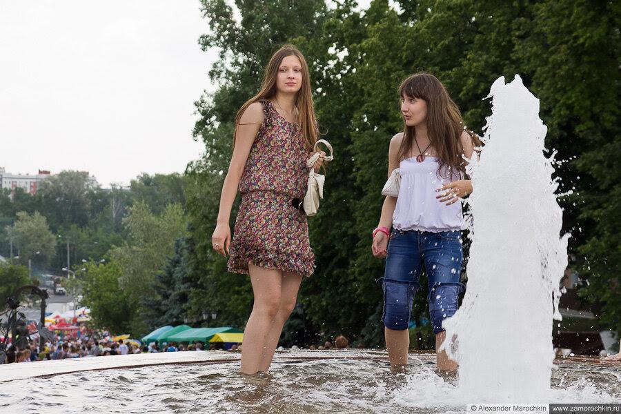Девушки в одежде купаются в фонтане