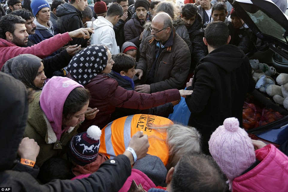 Refugees and migrants try to get food distributed by Greek volunteers after their arrival from the eastern Greek islands to the Athens' port of Piraeus