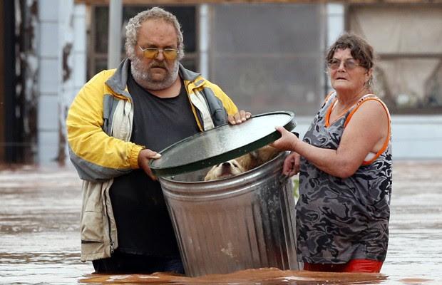 George e Susan Kruger fazem uma das três viagens com seus animais de casa alagada para abrigo no domingo (24) em Purcell, Oklahoma (Foto: AP)