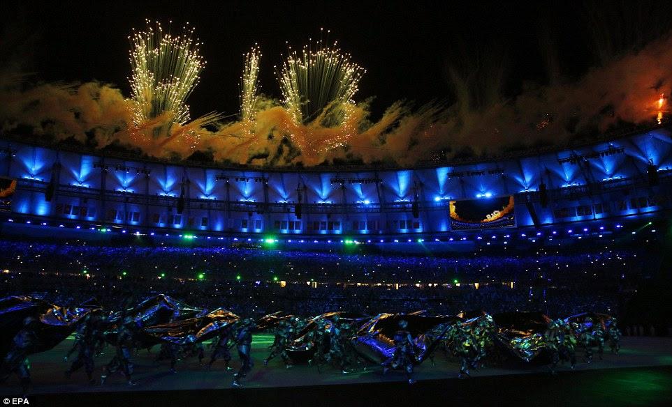 As palavras 'Rio' são mostrados em uma disoplay artifício acima do estádio, enquanto abaixo dos dançarinos