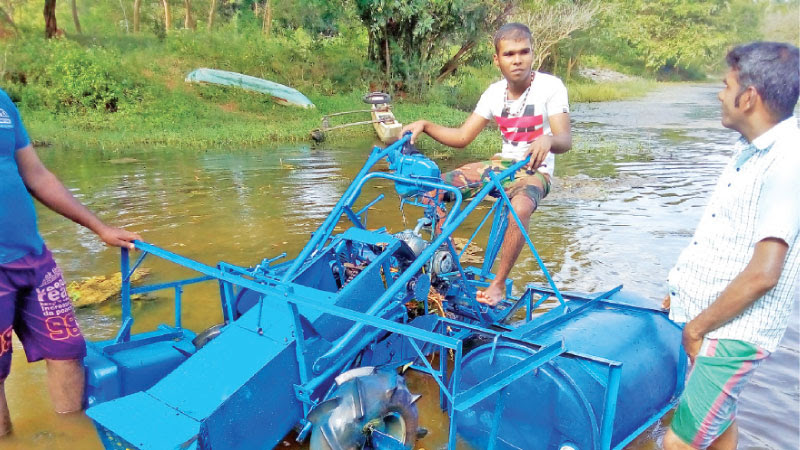 Darmapala with his aquatic weed harvester. Picture by Samantha Darmakeerthi, Thalawa Group Corr.