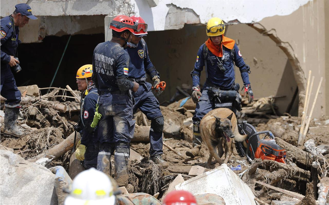 "Firefighters search for survivors in Mocoa, Colombia, Sunday, April 2, 2017. Colombia's President Juan Manuel Santos, who has declared Mocoa a disaster area, said that at least 207 were killed but that the death toll was changing ""every moment."" Authorities said another 200 people, many of them children, were injured and just as many were unaccounted for amid the destruction."