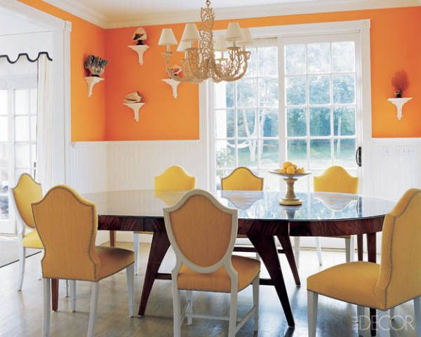 In a Hamptons cottage, Stephen Gambrel makes bright tangerine soothing by offsetting the vivid color with white wainscoting and an antique wood table.