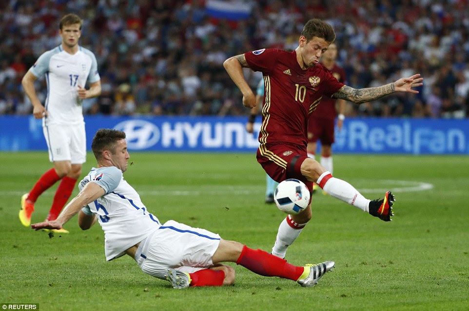 Gary Cahill thwarts a Russian attack as he slides in on forward Fedor Smolov early in the match at Stade Velodrome, Marseille