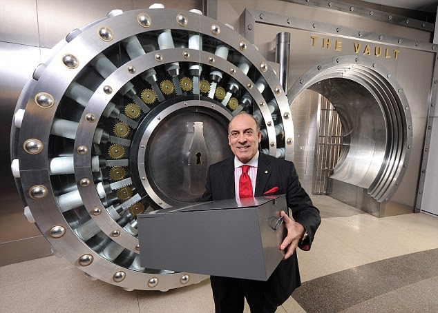 In the can: Coca-Cola CEO Muhtar Kent holds the metal box that supposedly contains the secret recipe, which has been moved from a bank vault to the company's Atlanta museum