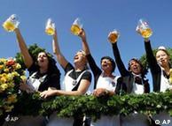 Oktoberfest waitresses raise beer mugs into the air
