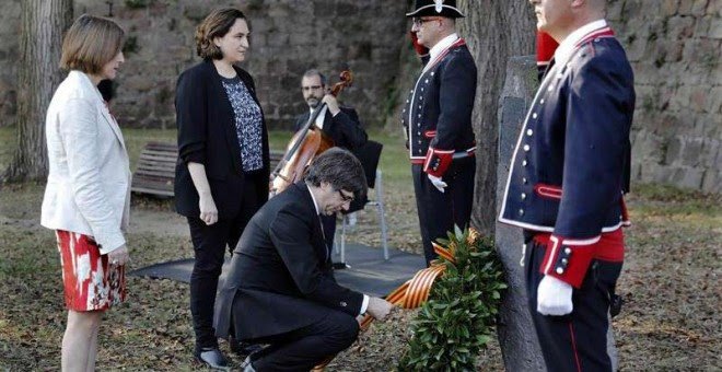 El presidente de la Generalitat, Carles Puigdemont, acompañado por la alcaldesa de Barcelona, Ada Colau y la presidenta del Parlament, Carme Forcadell, coloca unas flores en el lugar donde Lluis Companys fue fusilado.   EFE