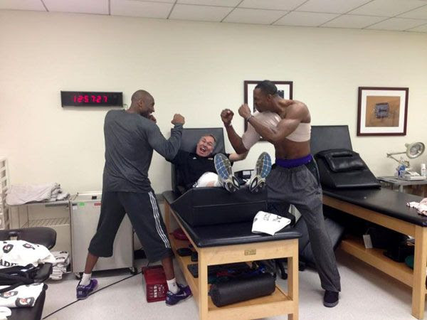Kobe Bryant and Dwight Howard pretend to brawl as Lakers coach Mike D'Antoni um, looks on.