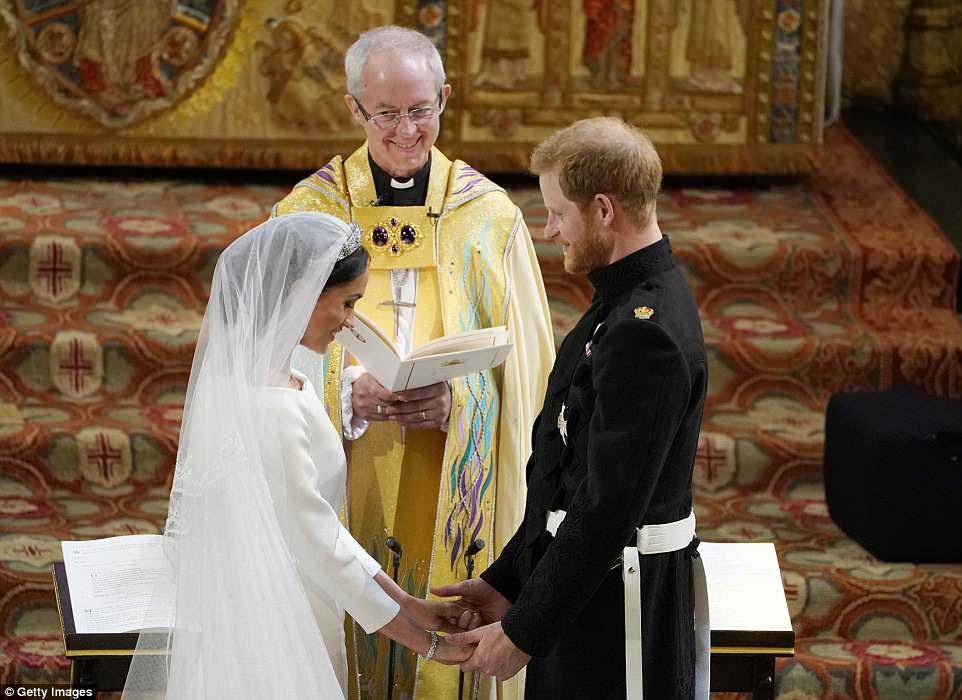 O arcebispo de Canterbury sorri enquanto o príncipe Harry e Meghan Markle estão no altar da capela de São Jorge