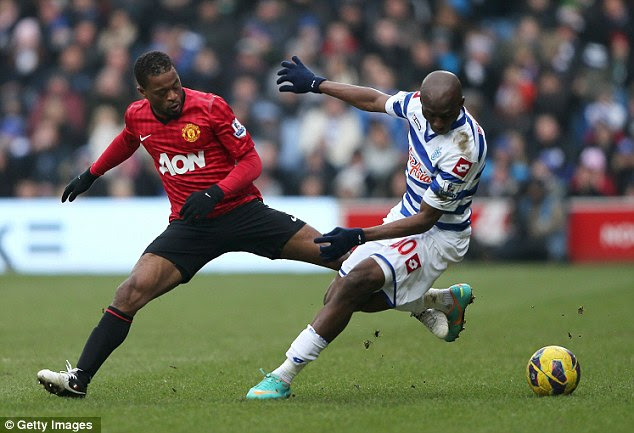 Tangled up: Patrice Evra challenges Stephane Mbia