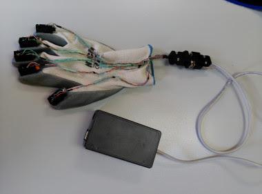 <p>Los dos componentes del sistema que porta el sordociego, con los estimuladores táctiles dispuestos sobre el guante directamente encima de las uñas. /UVa</p>