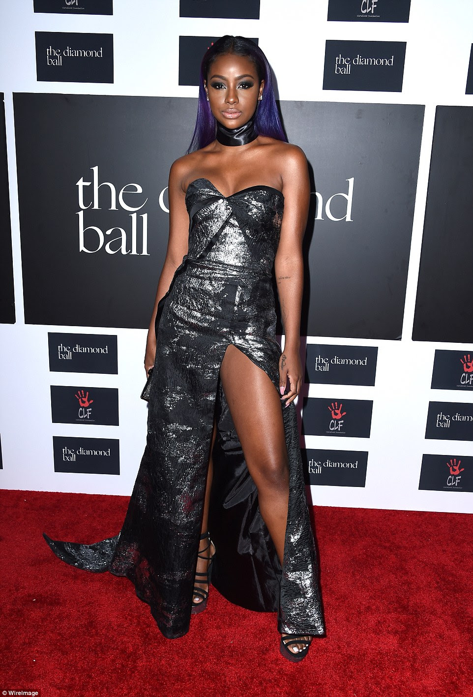 Shine bright: Singer Justine Skye wore a strapless silver dress and thick black choker