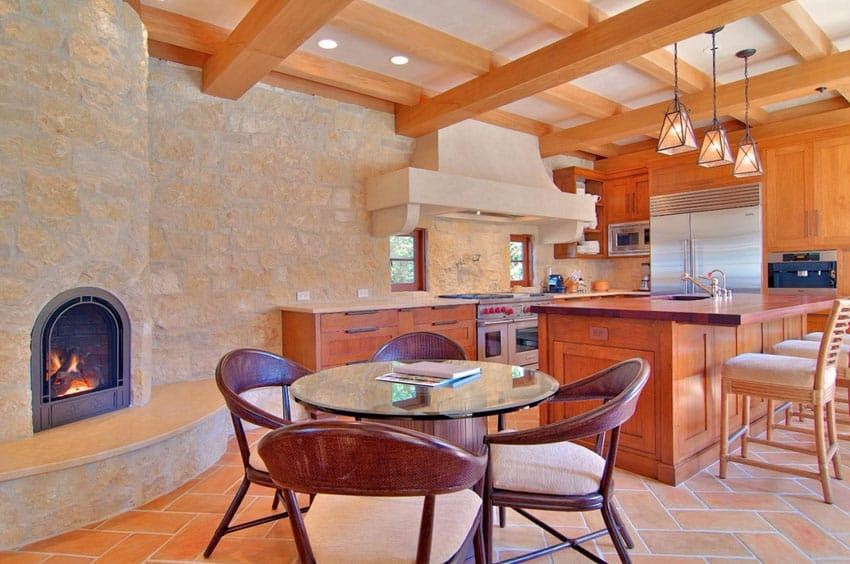 rustic kitchen with stone wall with fireplace wood beam ceiling