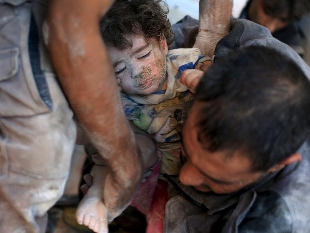 Menina é resgatada após bombardeio em área residencial na Síria (Foto: Bassam Khabieh / Reuters)