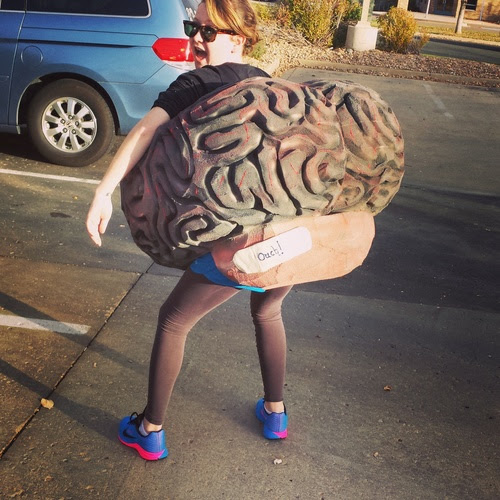 Mimi Hayes stands in a parking lot wearing a giant foam brain costume around her waist and torso.
