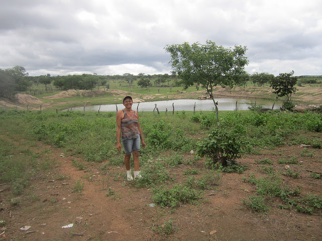 Normaleide de Oliveira stands in front of the pond on her farm that did not even run out of water during the six years of drought suffered by Brazil's Northeast region. Water availability is an advantage of family farmers in the Jacuípe river basin, compared to other areas of the country's semi-arid ecoregion. Credit: Mario Osava / IPS