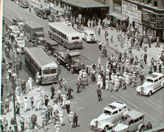Herald Square, 34th and Broadway, Manhattan. Looking down on busy intersection, people crossing, buses, trucks, cabs, other autos, Macy's entrance just visible with union picket in front.