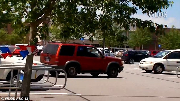 The red SUV speeds across the parking lot in Walmartin Asheville, North Carolina