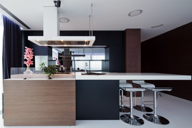 The kitchen area is backed by mirrored panels to reflect the large windows on opposite side, bouncing light around the deeper part of the layout. An asymmetrical white extractor echoes the shape of the white Corian countertop that protrudes long past the kitchen cabinetry to provide a dining area, and a tiny touch of stylish whimsy, in the form of a glazed mini courtyard, sits right in the central island, forming an unusual splashback to the hob.