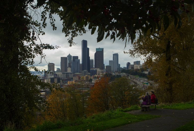 Two women on their way back from lunch relax for a few moments on a bench in Jose Rizal Park. (Ellen M. Banner/The Seattle Times)