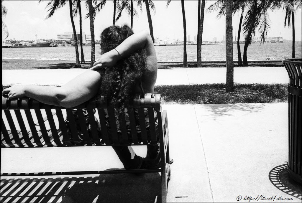 Woman resting on the bench in Bayfront park in Downtown Miami, Florida, USA, 2011. Street Photography of Miami, San Francisco and Key West by Emir Shabashvili, see http://street-foto.com, http://miamistreetphoto.com, http://miamistreetphotography.com or http://miamistreetphotographer.com