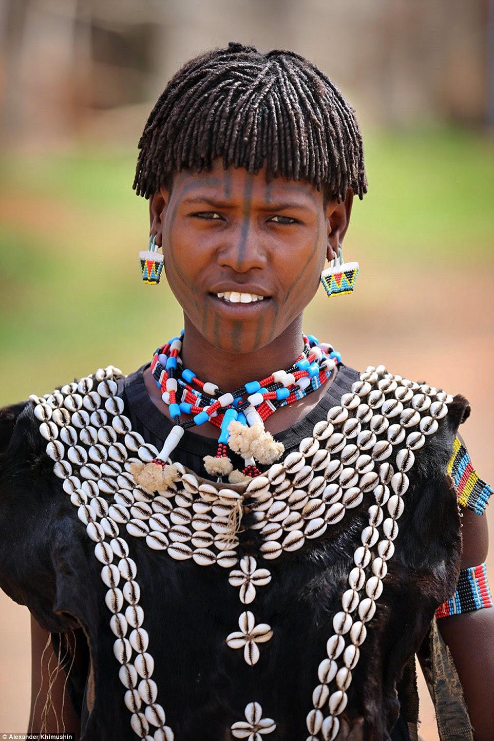 Vestindo uma roupa feita de conchas e peles uma tribo menina Tsemay usa pérolas em forma de bolsa em seus ouvidos (foto).  A população local, muitas vezes convidar o Sr. Khimushin para participar de suas antigas tradições