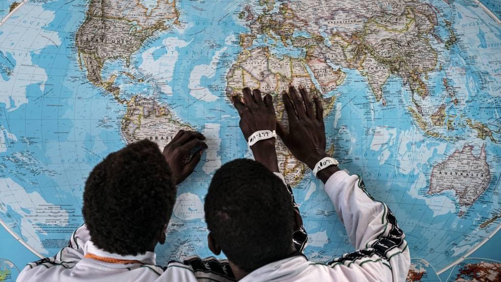 Dos menores de Gambia solicitantes de asilo en Italia, discuten sobre el viaje que han realizado en un mapa en el puerto de Pozzallo, Sicilia.