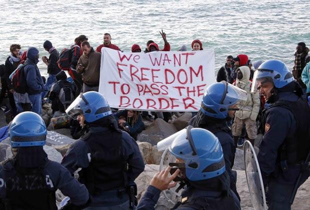 Migrantes e ativistas exibiram uma faixa com a frase em inglês 'Queremos a liberdade de atravessar a fronteira' depois de acompamento ser desmantelado na fronteira da Itália com a França (Foto: Eric Gaillard/ Reuters)
