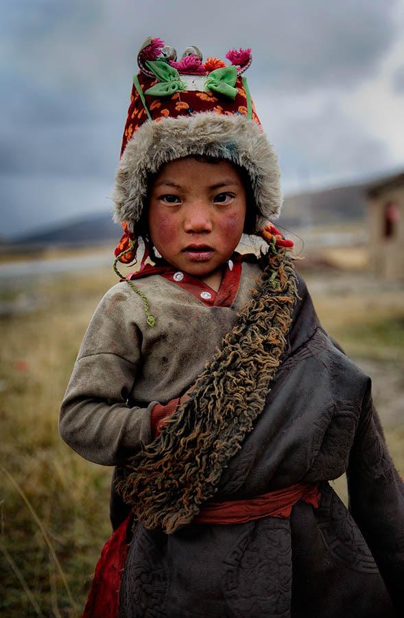 Tibetan kid on traditional clothes. Tibetan plateau
