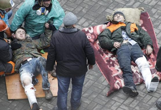 Injured men receive medical assistance in Independence Square in Kiev February 20, 2014. REUTERS-Vasily Fedosenko