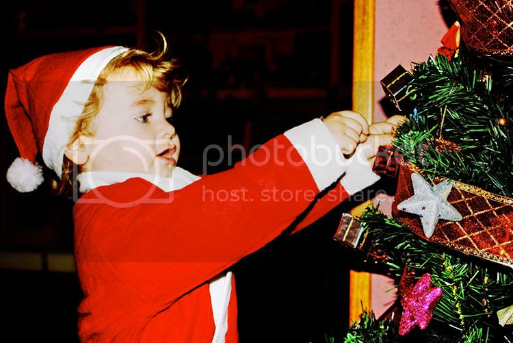 Niño vestido de Papá Noel colocando adornos en el árbol de Navidad