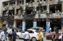 People walk on a street lined with a damaged building and destroyed cars after a blast at Marjeh Square in Damascus