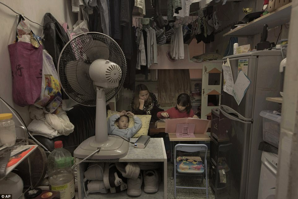 Li Suet-wen and her son, 6, and daughter, 8, live in a 120-square foot room crammed with a bunk bed, small couch, fridge, washing machine and small table in an aging walkup in Hong Kong