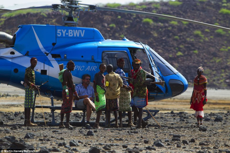 Curious: A group of Kenyan people gather around the safari helicopter for a closer look after it lands