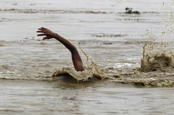 A man swims in the flooded waters of river Yamuna to retrieve floating watermelons in New Delhi, June 18, 2013. REUTERS-Anindito Mukherjee
