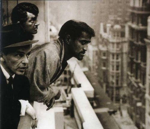 Dean Martin, Frank Sinatra, and Sammy Davis Jr. look out into the busy streets of the city.