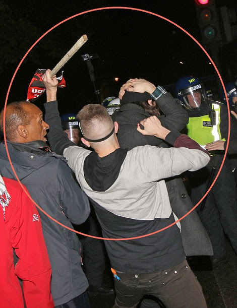 One protester is seen appearing to attempt to strike police officers with a long piece of wood