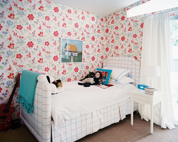 Cath Kidston - A white upholstered bed accented by floral-patterned wallpaper and a blue throw