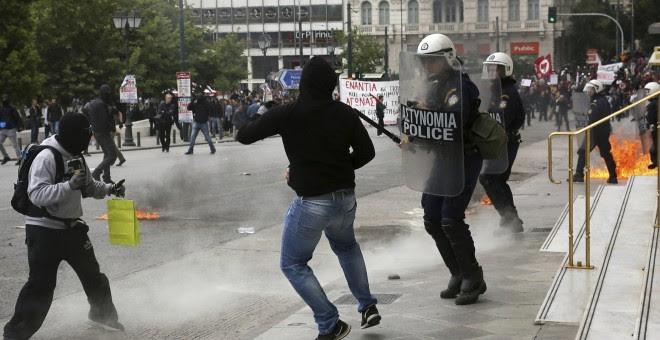 Varios activistas se enfrentan a la policía antidisturbios mientras participan en una manifestación durante la huelga general de 24 horas en Atenas (Grecia).EFE/Alexandros Vlachos