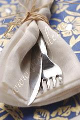 Cutlery in a linen napkin on blue