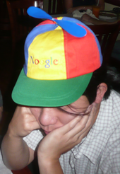 "Asian man in his twenties wearing a blue, green, yellow and red propellor hat that says ""Noogle"""