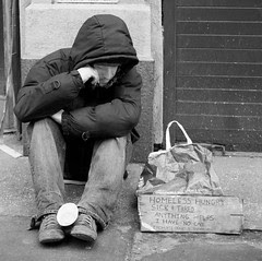 Homeless young man with a Collection Cup