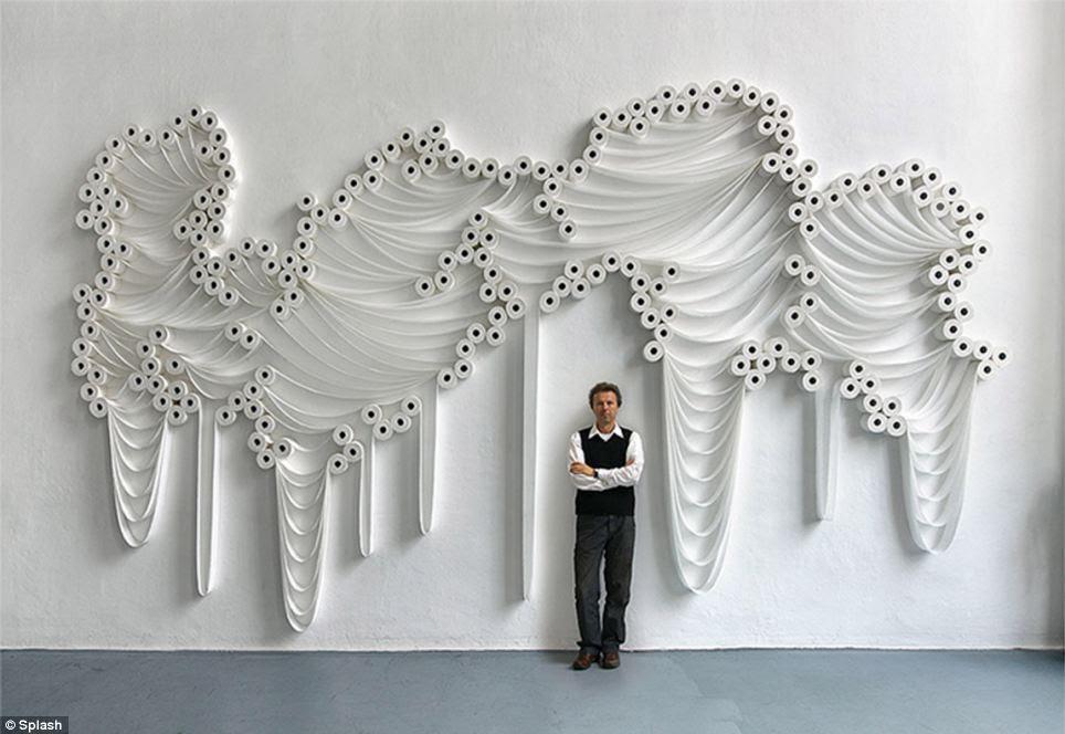 Loo-py art: Turkish artist Sakir Gkceba posing next to one of his installations created using hundreds of toilet rolls