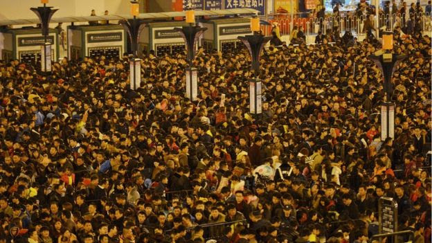 Passengers wait to enter a railway station in Guangzhou
