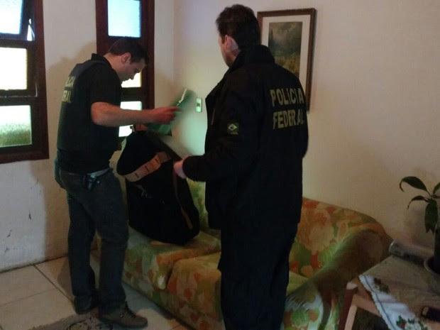 Policiais federais apreendem documentos na casa de suspeito no Rio Grande do Sul durante operação contra fraude em urnas eletrônicas (Foto: Polícia Federal/Divulgação)