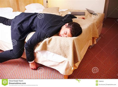 overworked tired businessman lying   bed stock image