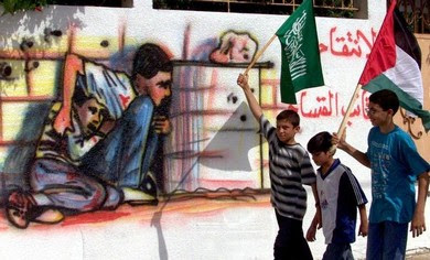 Palestinian boys carrying Hamas flags in the Gaza Strip walk past graffiti showing Muhammad al-Dura.