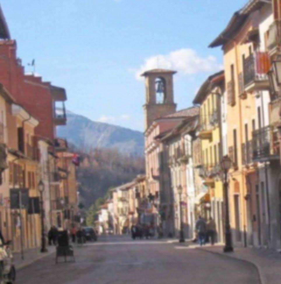 Uma rua italiano uma vez agradável em Amatrice preenchido com edifícios cor de terracota (à esquerda) agora aparece como uma massa de entulho cinza (à direita)